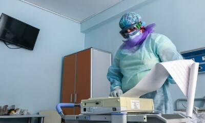 doctor in protective clothing a mask and glasses looks at the printout of an electrocardiogram on a t20 E0PAYY