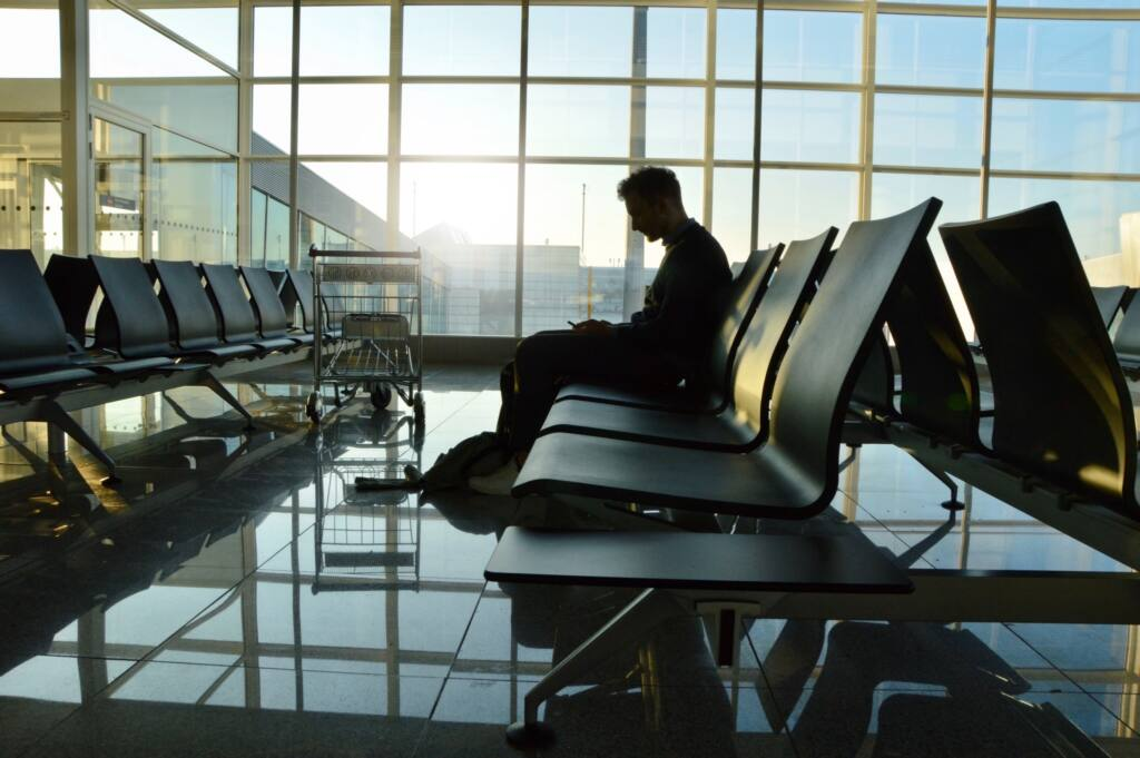 photo of a young man waiting alone at an empty airport looking out through the big windows at the t20 WgnrQw